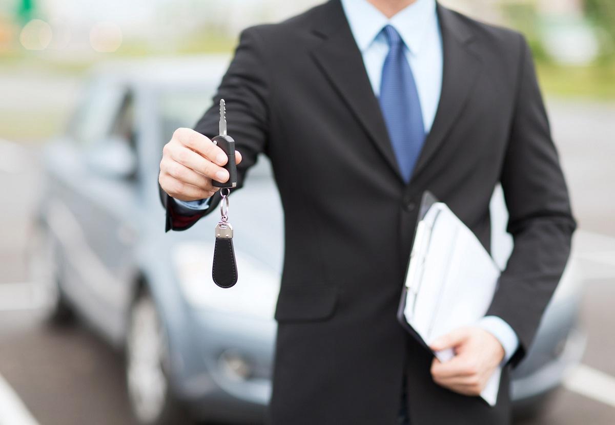 mężczyzna wręczający kluczyki do wypożyczonego samochodu na okres długoterminowy